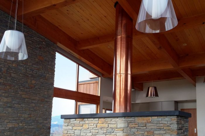 NZ Living Homes - Custom design copper chimney flue and schist fireplace